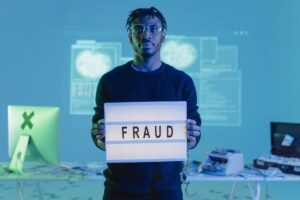 man holding fraud sign in front of computer and cash