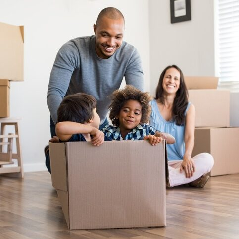 family of four having fun with moving boxes in home